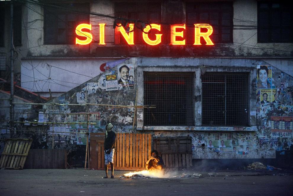 7.BANGLADESZ, Dhaka, 4 stycznia 2014: Mężczyźni grzeją się przy ognisku rozpalonym na ulicy. AFP PHOTO/Roberto SCHMIDT