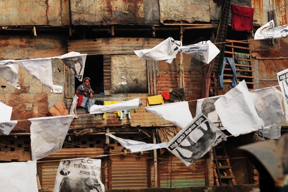 8.BANGLADESZ, Dhaka, 3 stycznia 2015: Mieszkanka slumsów w oknie swojego domu. AFP PHOTO/Munir uz ZAMAN