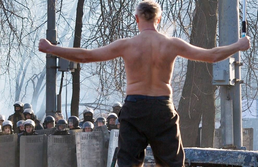 9.UKRAINA, Kijów, 20 stycznia 2014: Półnagi mężczyzna stojący przed oddziałem milicji. AFP PHOTO/ SERGEI SUPINSKY