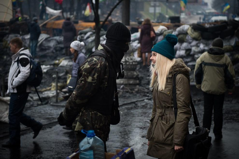 10.UKRAINA, Kijów, 12 lutego 2014: Kobieta rozmawia z protestującym na Majdanie mężczyzną. AFP PHOTO / MARTIN BUREAU