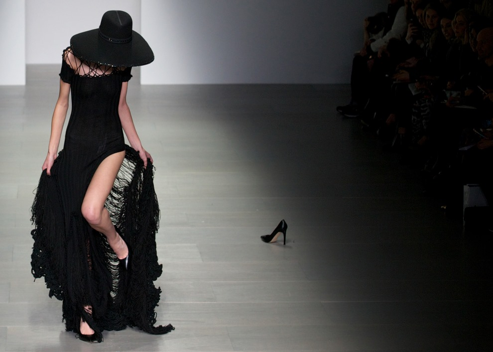 10. WIELKA BRYTANIA, Londyn, 15 lutego 2014: Modelka stara się wyplątać obcas buta z sukienki. AFP PHOTO / ANDREW COWIE