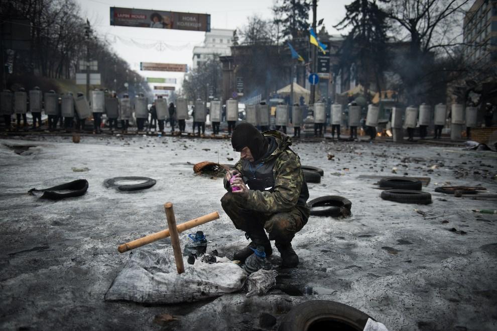 11.UKRAINA, Kijów, 13 lutego 2014: Uczestnik protestów zapala znicz. AFP PHOTO / MARTIN BUREAU