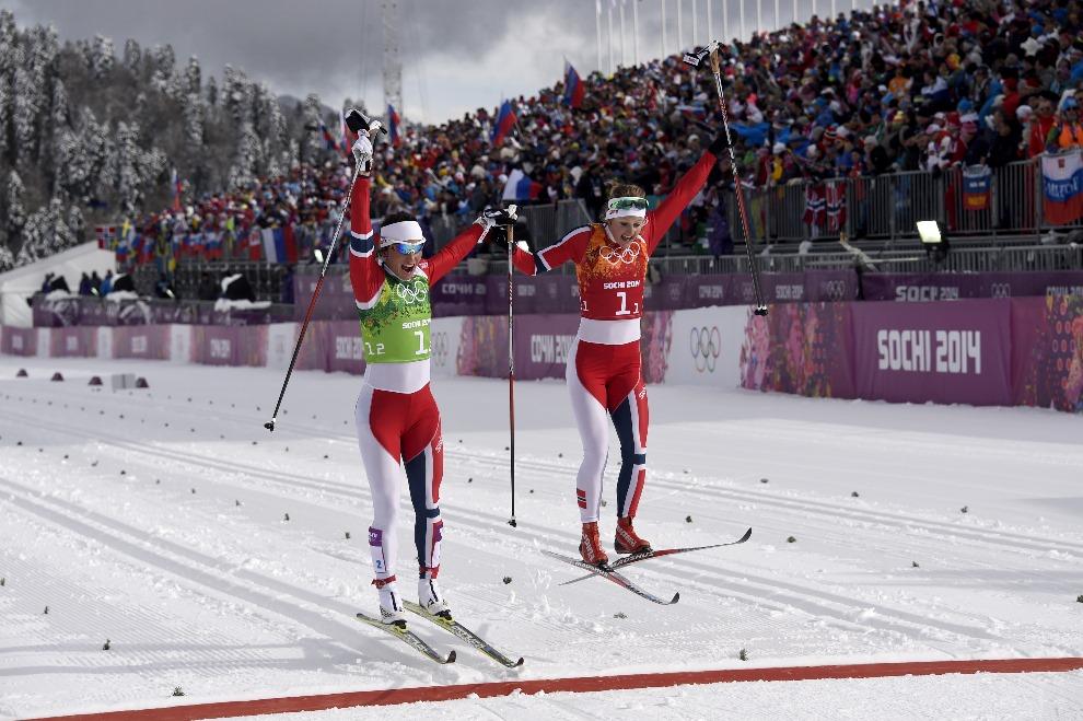 12.ROSJA, Krasna Polana, 19 lutego 2014: Marit Bjoergen (po lewej) i Ingvild Flugstad Oestberg cieszą się wbiegając na metę. AFP PHOTO / ODD ANDERSEN