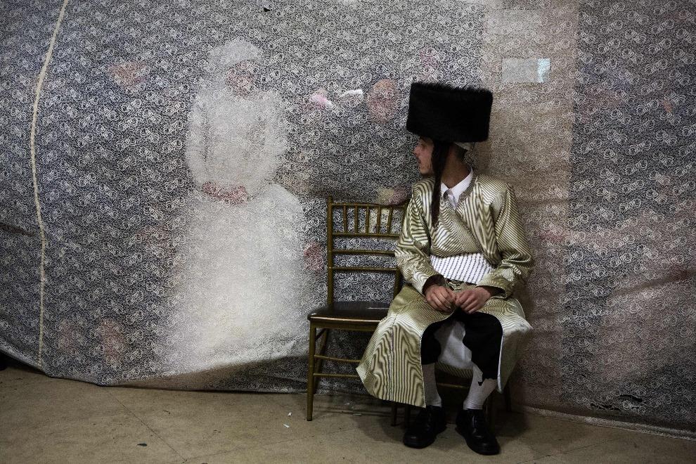 12. IZRAEL, Jerozolima, 18 lutego 2014: Rivka Hannah (Hofman) patrzy zza zasłony na swojego przyszłego męża, Aharona Kroisa. AFP PHOTO/MENAHEM KAHANA