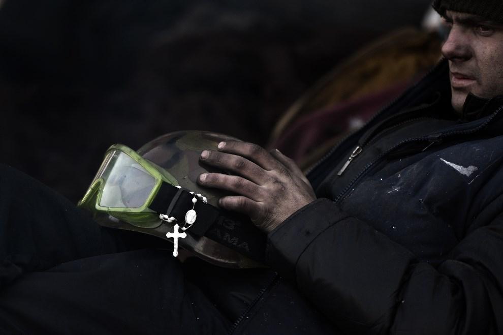 12. URKAINA, Kijów, 5 lutego 2014: Jeden z protestujących odpoczywa na barykadzie. AFP PHOTO / ARIS MESSINIS