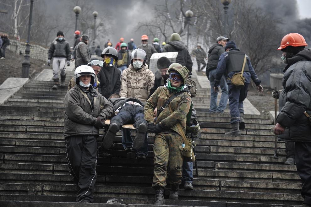 12.UKRAINA, Kijów, 20 lutego 2014: Protestujący niosą rannego towarzysza. AFP PHOTO / LOUISA GOULIAMAKI