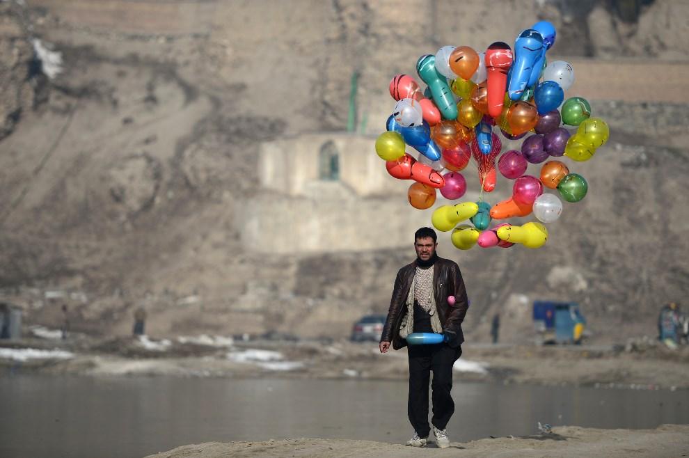 13.AFGANISTAN, Kabul, 10 lutego 2014: Afgańczyk z balonami na przedmieściach Kabulu. AFP PHOTO/ Wakil Kohsar