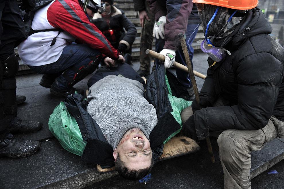 13.UKRAINA, Kijów, 20 lutego 2014: Ranny mężczyzna ewakuowany obszaru gdzie toczą się walki. AFP PHOTO / LOUISA GOULIAMAKI