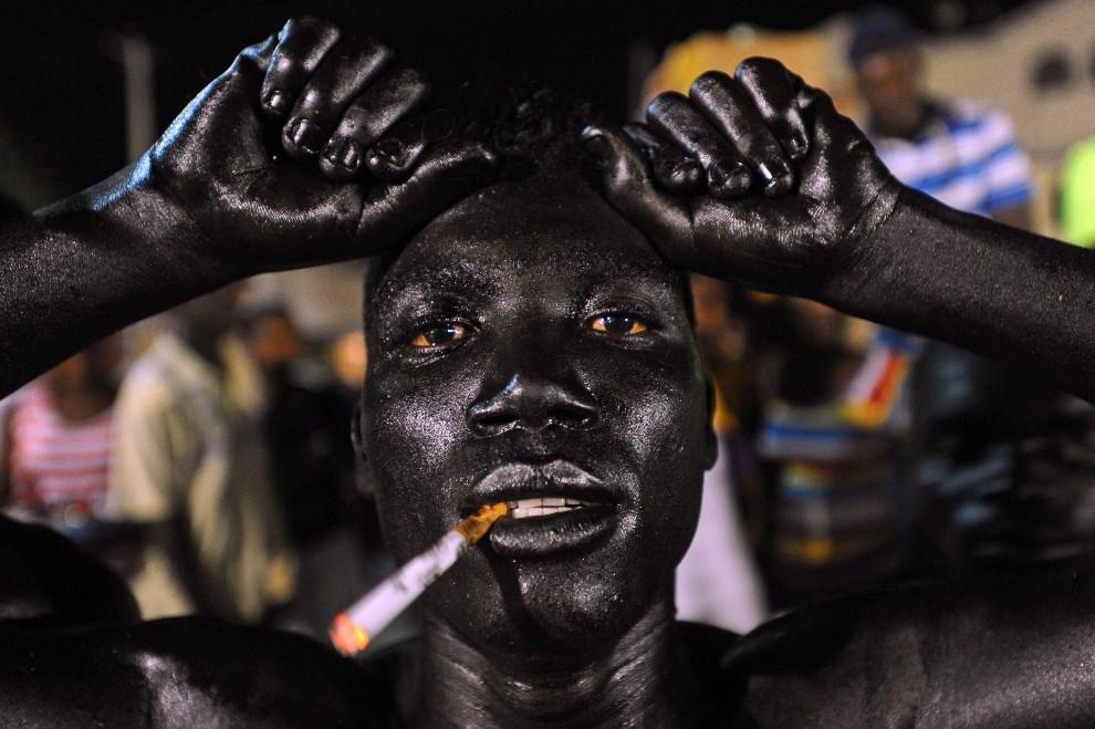 13.HAITI, Port-au-Prince, 22 lutego 2014: Mężczyzna pomalowany olejem silnikowym, podczas karnawału. AFP PHOTO/Hector RETAMAL