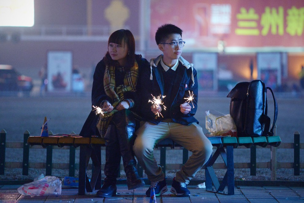 14.CHINY, Lanzhou, 30 stycznia 2014: Para siedzące na ławce z zapalonymi zimnymi ogniami. AFP PHOTO / WANG ZHAO