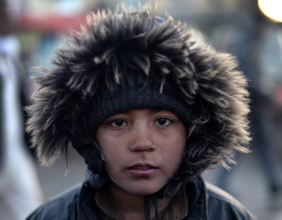14.AFGANISTAN, Kabul, 9 lutego 2014: Afgański chłopiec na bazarze w Kabulu. AFP PHOTO/Wakil KOHSAR