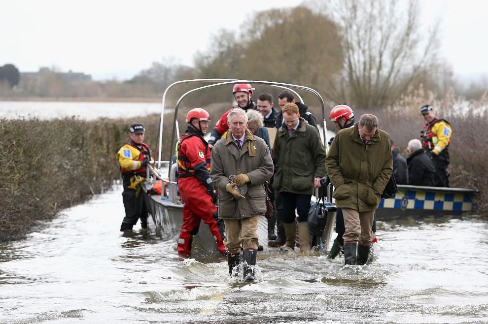 14.WIELKA BRYTANIA, Muchleney, 4 lutego 2014: Książę Karol wysiada z łodzi policyjnej podczas wizyty na zalanych terenach. (Foto: Chris Jackson/Getty Images)