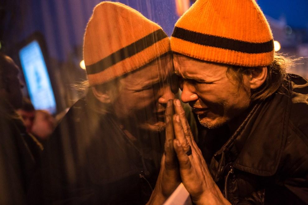 14.UKRAINA, Kijów, 21 lutego 2014: Mężczyzna przy samochodzie wiozącym ciało Ustima Hołodyniuka (19 lat) - jednej z ofiar walk na Majdanie. (Foto: Brendan Hoffman/Getty Images)