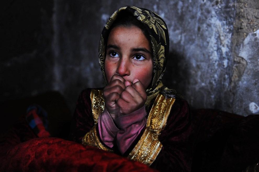 15.AFGANISTAN, Herat, 7 lutego 2014: Dziewczynka ogrzewająca się przy piecyku. AFP PHOTO/Aref Karimi