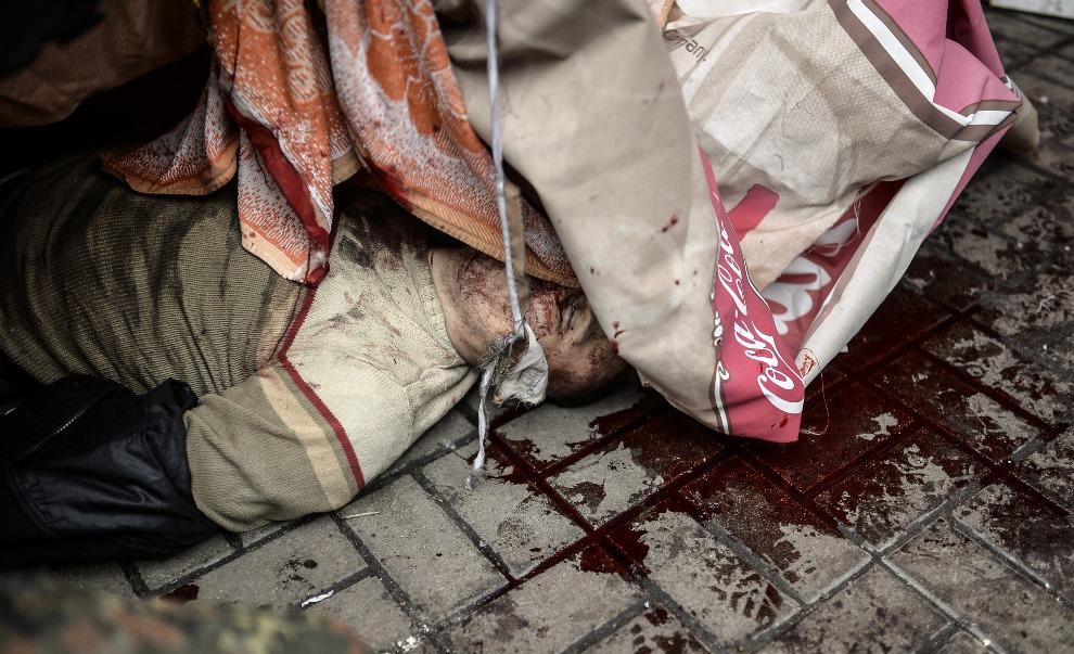 15.UKRAINA, Kijów, 20 lutego 2014: Ciało mężczyzny zabitego w trakcie walk. AFP PHOTO/BULENT KILIC