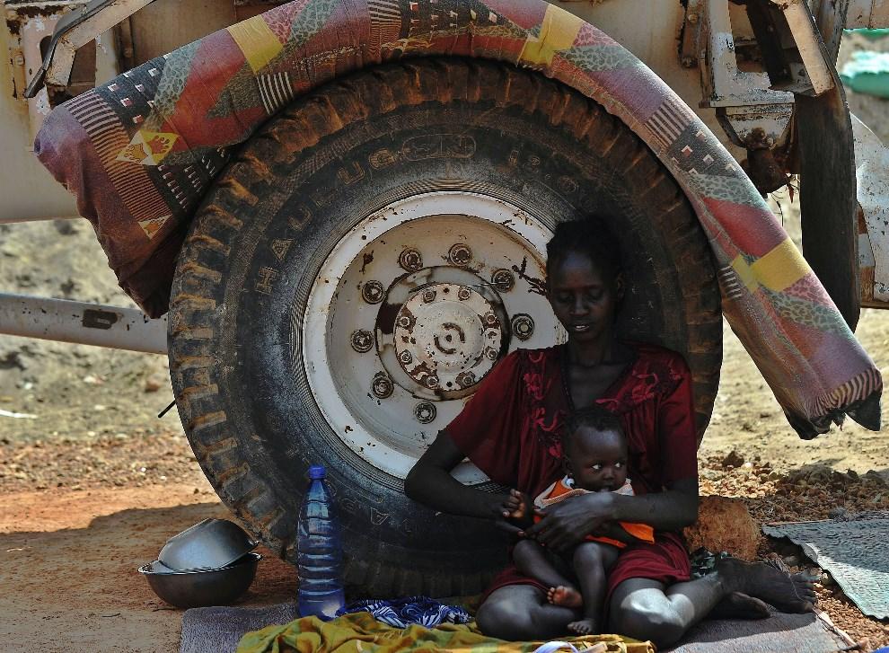 16.SUDAN POŁUDNOWY, Rumbek, 18 lutego 2014: Kobieta z plemienia Nuer w odpoczywa przy ciężarówce należącej do lokalnej misji ONZ. AFP PHOTO/Tony KARUMBA