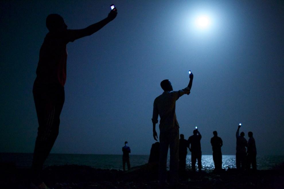 17.DŻIBUTI, Dżibuti: Afrykańscy imigranci, którzy przybili nocą do brzegu w Dżibuti, szukają zasięgu dla sieci komórkowej. AFP PHOTO/ John Stanmeyer - VII Photo   Agency