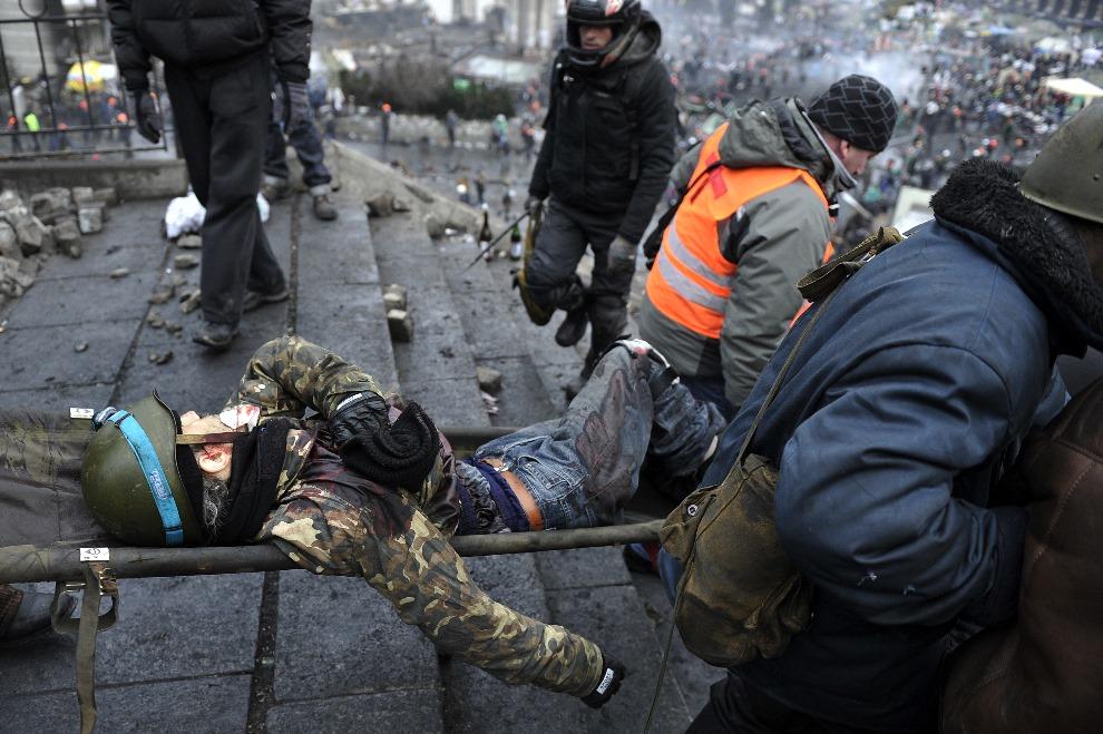 17.UKRAINA, Kijów, 20 lutego 2014: Ewakuacja rannego mężczyzny z miejsca walk. AFP PHOTO / LOUISA GOULIAMAKI
