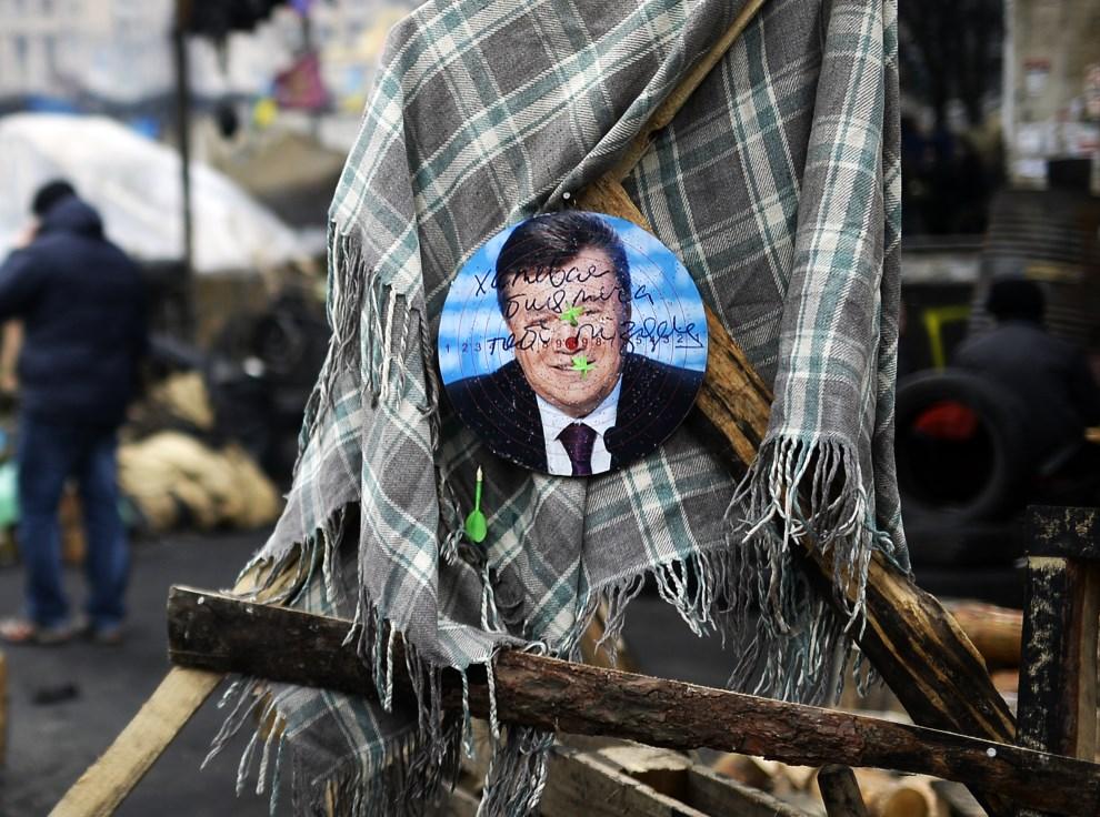 17.UKRAINA, Kijów, 25 lutego 2014: Zdjęcie Wiktora Janukowycza na tarczy. AFP PHOTO/BULENT KILIC
