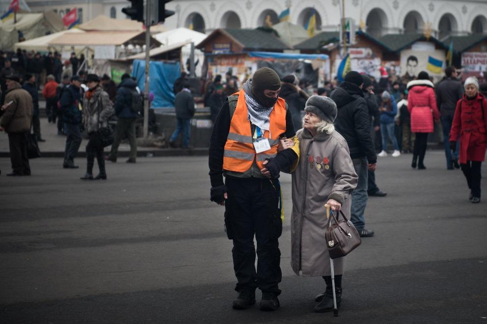 18.UKRAINA, Kijów, 15 lutego 2014: Jeden z protestujących rozmawia ze starszą kobietą. AFP PHOTO / MARTIN BUREAU