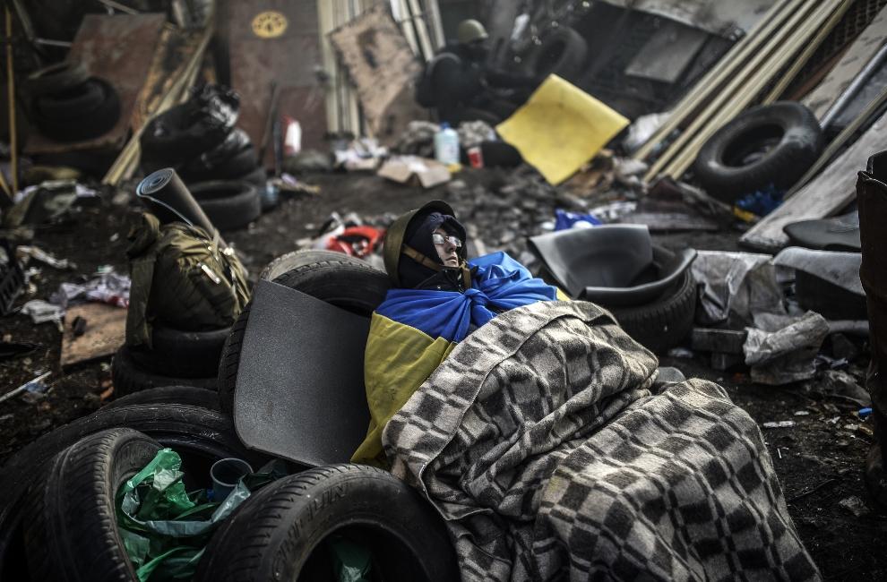 19.UKRAINA, Kijów, 21 lutego 2014: Mężczyzna śpiący na barykadzie. AFP PHOTO / BULENT KILIC