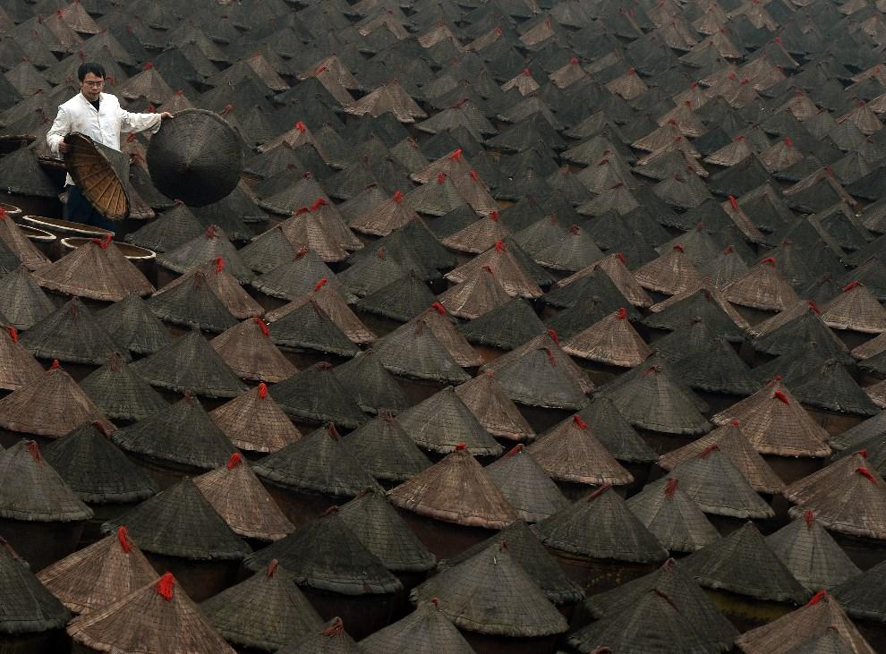 19.CHINY, Chongqing, 22 lutego 2014: Mężczyzna między glinianymi pojemnikami z fermentującymi ostrymi papryczkami używanymi do produkcji sosów. AFP PHOTO/Mark   RALSTON