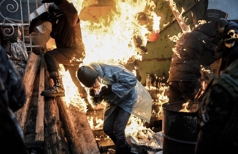 1.UKRAINA, Kijów, 20 lutego 2014: Płonący przeciwnicy rządu podczas walk na barykadzie. AFP PHOTO/BULENT KILIC