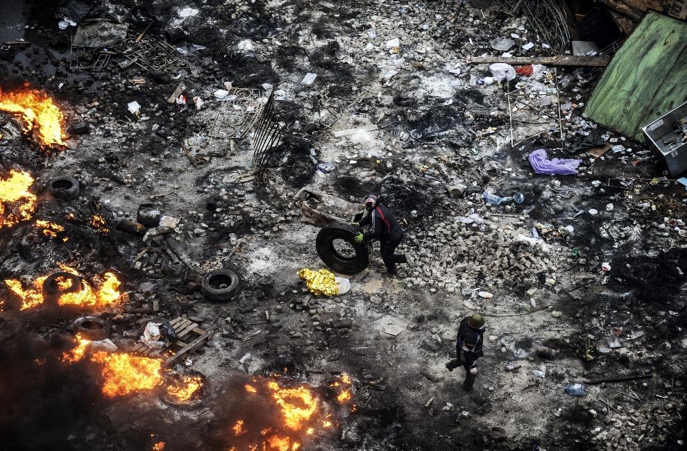 20.UKRAINA, Kijów, 20 lutego 2014: Mężczyźni dokładają opony do płonącej barykady. AFP PHOTO/BULENT KILIC