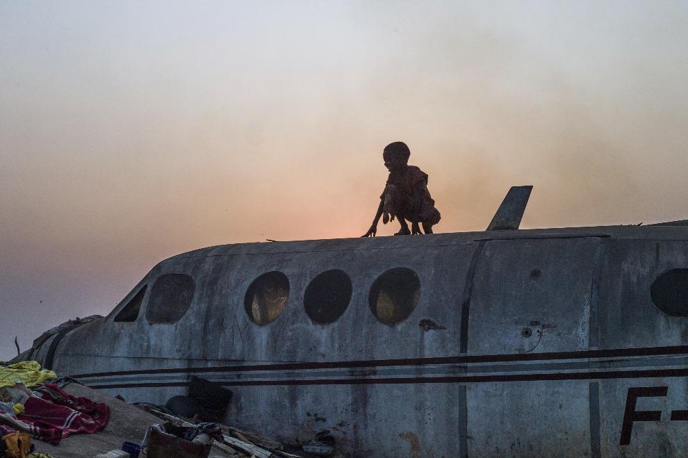 20. REPUBLIKA ŚRODKOWOAFRYKAŃSKA, Bangui, 20 lutego 2014: Chłopiec na dachu samolotu w obozie dla uchodźców. AFP PHOTO / FRED DUFOUR