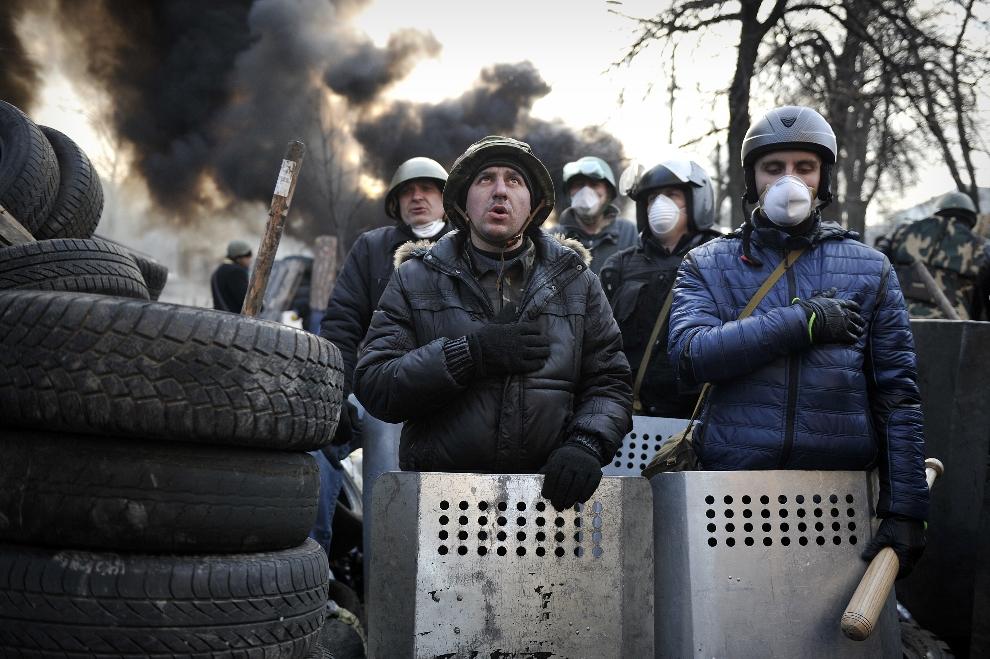 20.UKRAINA, Kijów, 21 lutego 2014: Protestujący śpiewający hymn państwowy. AFP PHOTO / LOUISA GOULIAMAKI