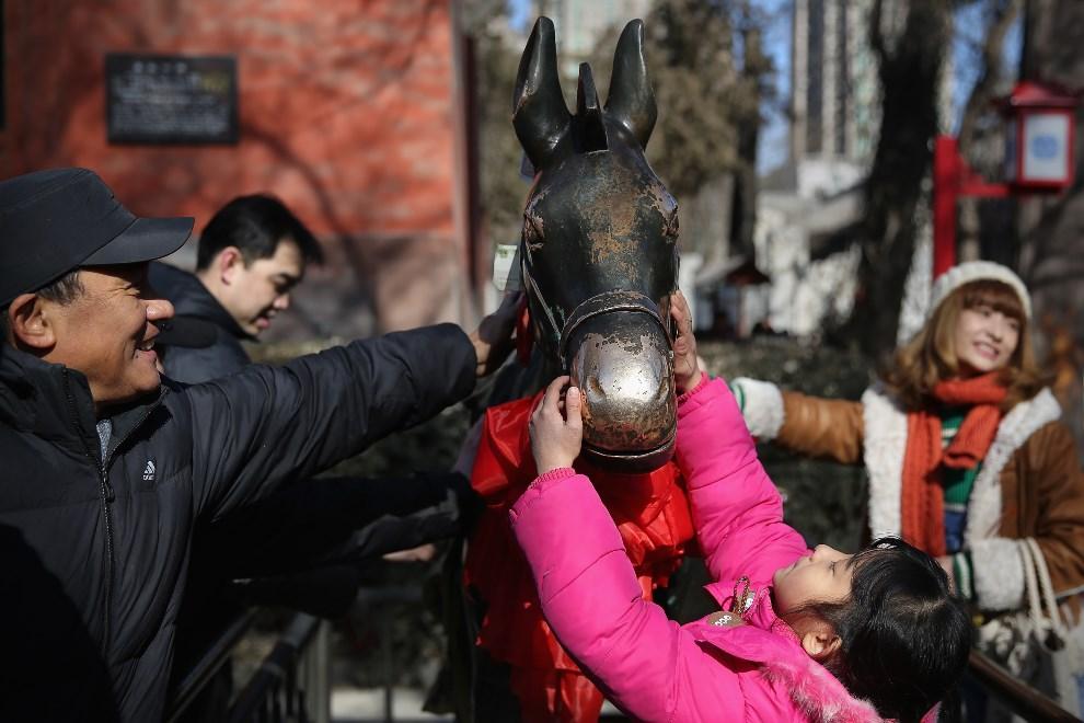 20.CHINY, Pekin, 4 lutego 2014: Turyści gładzą pysk posągu konia. (Foto:  Feng Li/Getty Images)