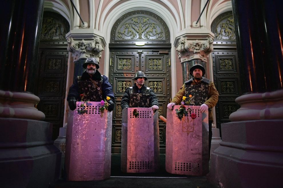 21.UKRAINA, Kijów, 23 lutego 2014: Przeciwnicy rządu pilnują dostępu do jednego z budynków administracji. (Foto: Jeff J Mitchell/Getty Images)