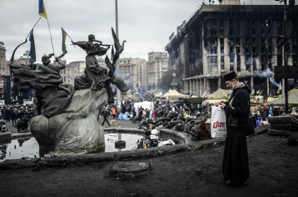 23.UKRAINA, Kijów, 25 lutego 2014: Kapłan na Placu Niepodległości. AFP PHOTO/BULENT KILIC