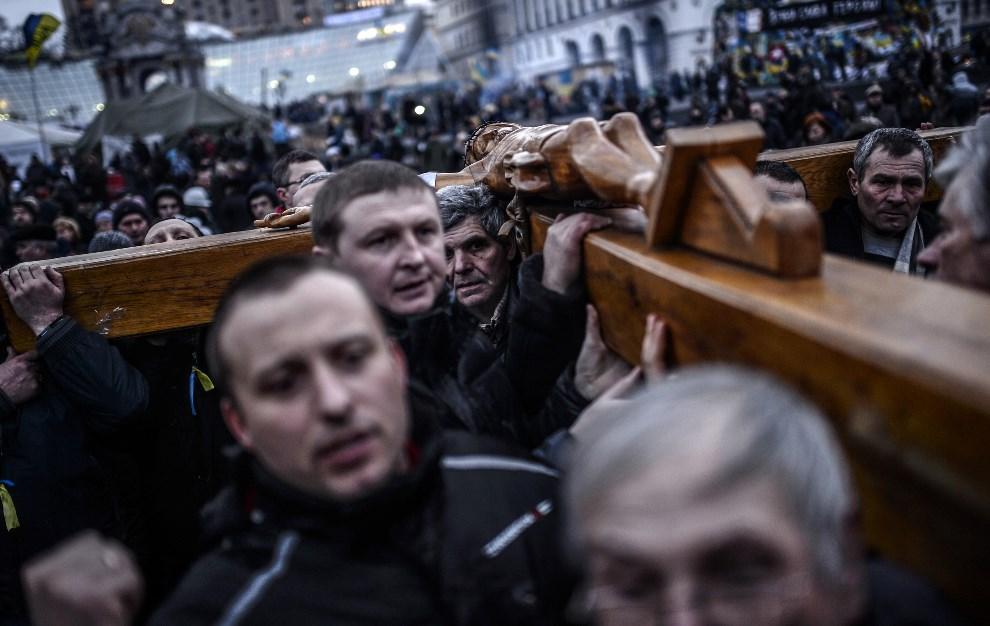 24.UKRAINA, Kijów, 25 lutego 2014: Uczestnicy procesji niosący krzyż. AFP PHOTO / BULENT KILIC