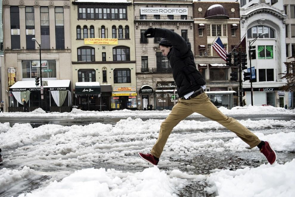 24.USA, Waszyngton, 13 lutego 2014: Mężczyzna skaczący przez śnieg na Connecticut Avenue. AFP PHOTO / BRENDAN SMIALOWSKI