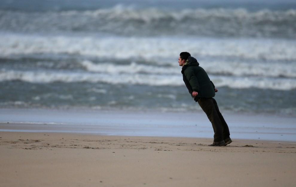 25.WIELKA BRYTANIA, Hayle, 8 lutego 2014: Mężczyzna na plaży opiera się podmuchom wiatru. (Foto: Matt Cardy/Getty Images)