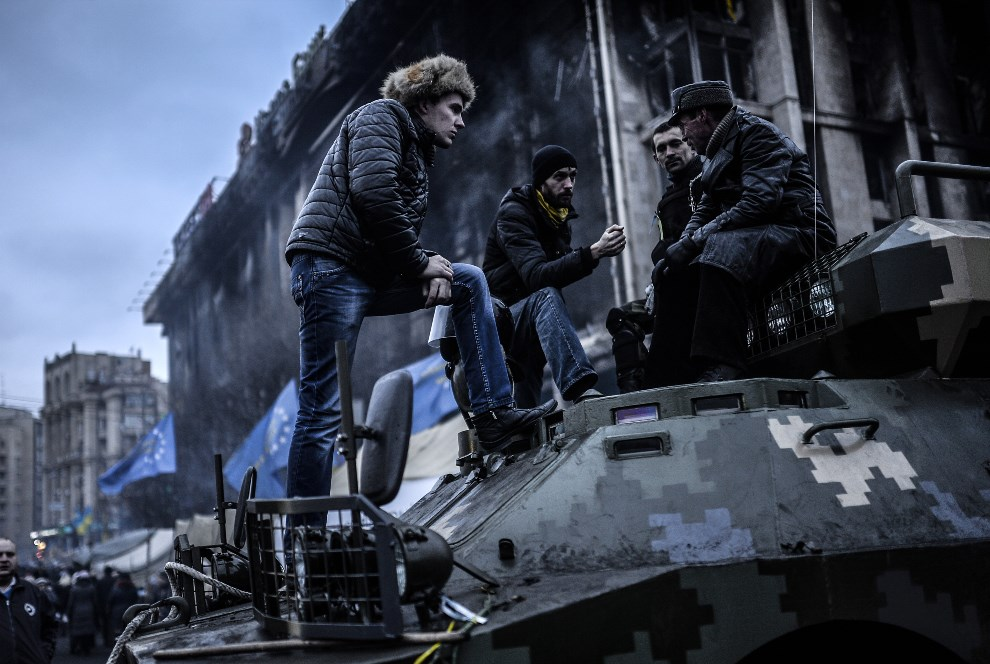 26.UKRAINA, Kijów, 25 lutego 2014: Ludzie odpoczywający na transporterze opancerzonym. AFP PHOTO / BULENT KILIC