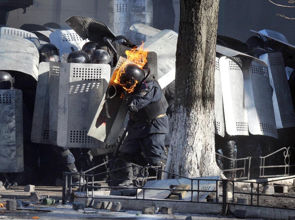 26.UKRAINA, Kijów, 18 lutego 2014: Policjant z płonącym hełmem. AFP PHOTO/GENYA SAVILOV