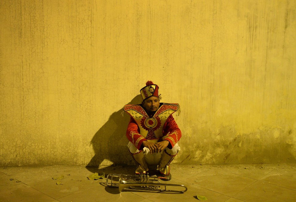 27. INDIE, Nowe Delhi, 28 stycznia 2014: Muzyk orkiestry weselnej czeka na występ. AFP PHOTO/SAJJAD HUSSAIN