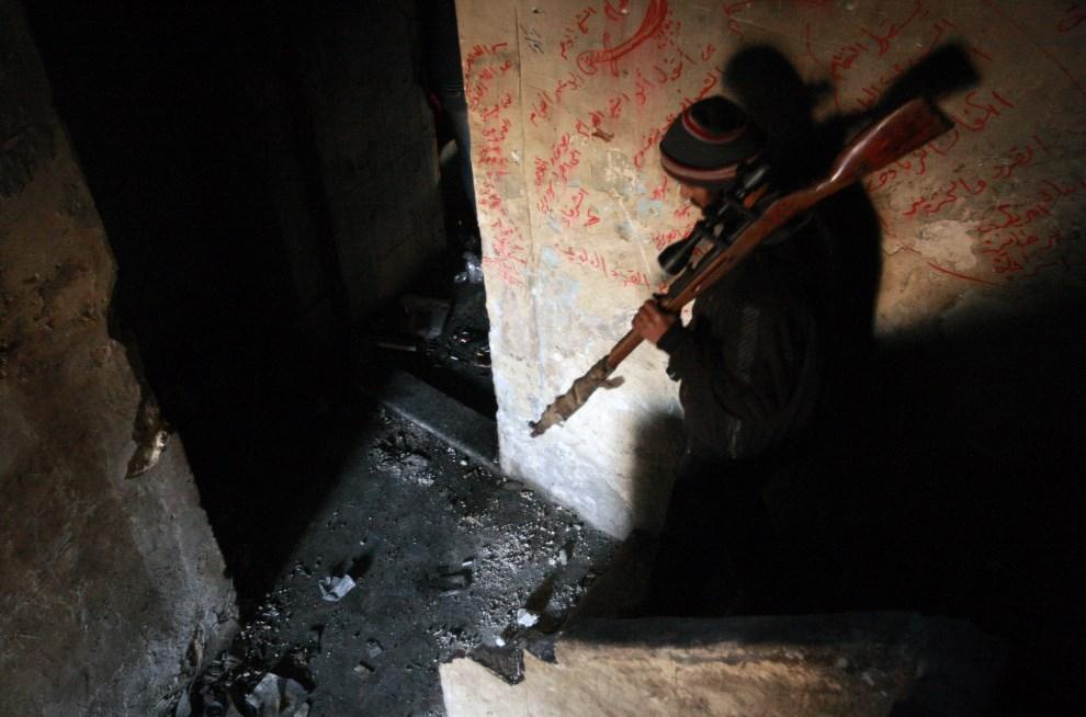 2.SYRIA, Aleppo, 9 lutego 2014: Snajper opuszcza swoje stanowisko w jednym z budynków. AFP PHOTO/MAHMUD ABDEL RAHMAN