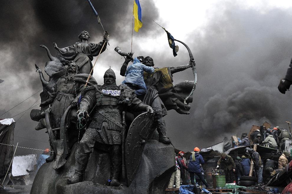 2.UKRAINA, Kijów, 20 lutego 2014: Protestujący zebrani w centrum Kijowa w pobliżu jednej z barykad. AFP PHOTO / LOUISA GOULIAMAKI
