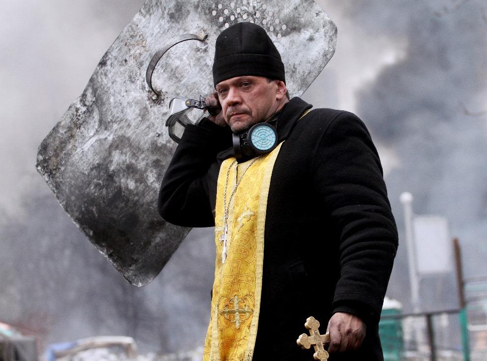 2. UKRAINA, Kijów, 20 lutego 2014: Duchowny trzymający tarczę podczas walk w Kijowie. AFP PHOTO/ SERGEY GAPON