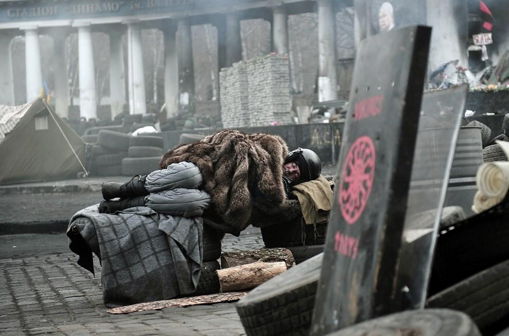 2.UKRAINA, Kijów, 27 lutego 2014: Mężczyzna śpiący na barykadzie w pobliżu stadionu Dynamo Kijów. AFP PHOTO/ LOUISA GOULIAMAKI