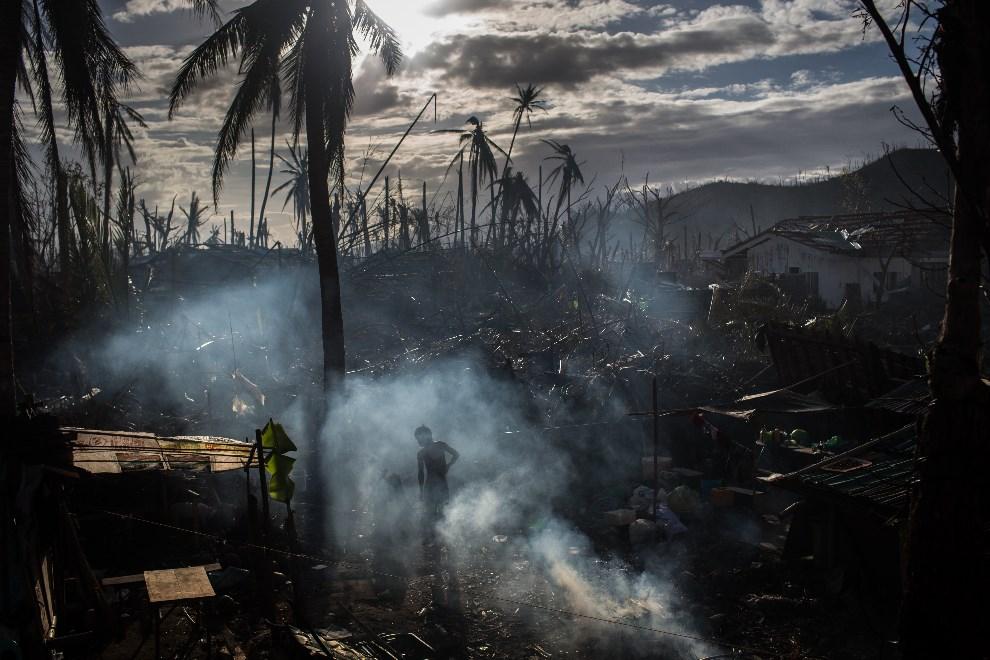 2.FILIPINY, Tanauan, 19 listopada 2013: Mężczyzna porządkuje pozostałości po swoim domu zniszczonym przez tajfun. (Foto: Chris McGrath/Getty Images)