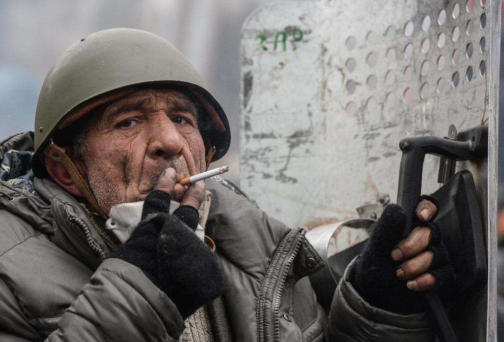 30.UKRAINA, Kijów, 20 lutego 2014: Mężczyzna na barykadzie w trakcie zawieszenia walk. AFP PHOTO / DMITRY SEREBRYAKOV