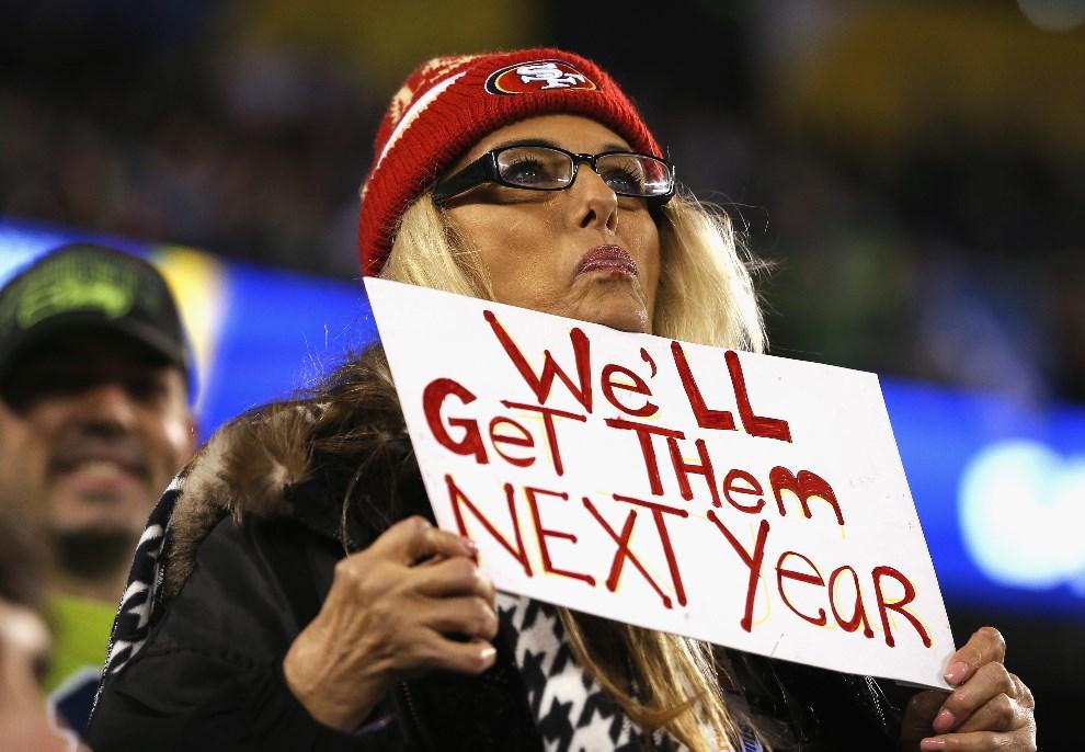 """31.USA, East Rutherford, 2 lutego 2014: Kibicka w czapce zespołu San Francisco 49ers trzyma tabliczkę z napisem: """"Dorwiemy ich w przyszłym roku"""". (Foto: Kevin C. Cox/Getty Images)"""