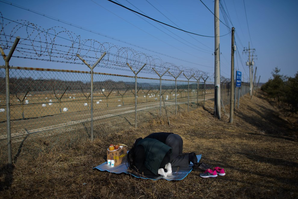 32.KOREA POŁUDNIOWA, Imjingak, 31 stycznia 2014: Pochodzący z Korei Północnej, Kang Myeong-wook i jego wnuczka, modlą się zwróceni w kierunku granicy z Północą.   AFP PHOTO / Ed Jones