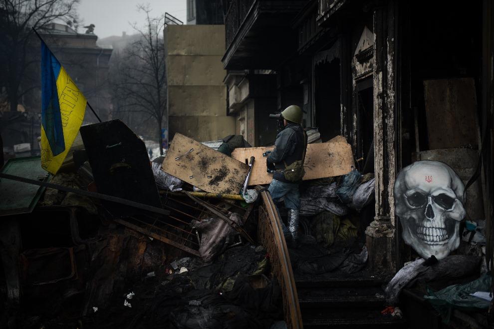 32.UKRAINA, Kijów, 12 lutego 2014: Jeden z protestujących na barykadzie. AFP PHOTO / MARTIN BUREAU