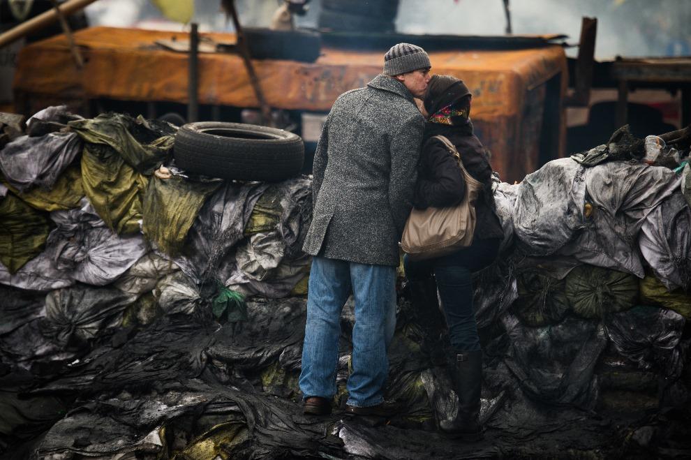 33.UKRAINA, Kijów, 14 lutego 2014: Mężczyzna całujący kobietę na barykadzie w centrum Kijowa. AFP PHOTO / MARTIN BUREAU