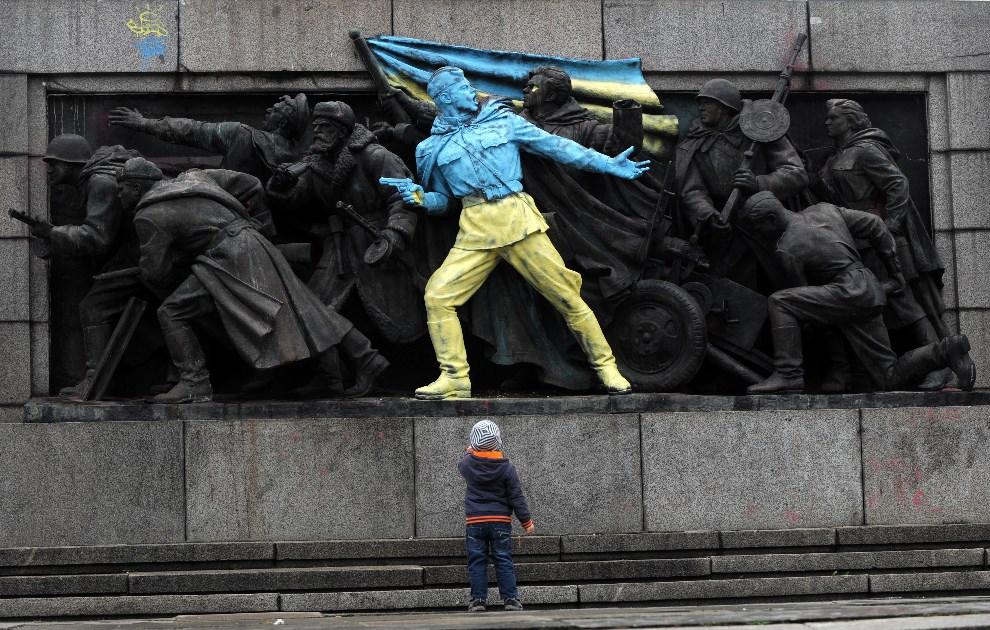 34.BUŁGARIA, Sofia, 23 lutego 2014: Chłopiec patrzy na pomnik Armii Czerwonej pomalowany w państwowych kolorach Ukrainy. AFP PHOTO / NIKOLAY DOYCHINOV
